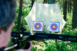 Man aiming crossbow at targets in summer forest poster