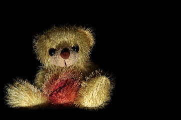 yellow bear with ripped up stomach on a black background