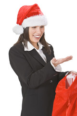 Young woman in a red hat discovering gifts in Santa's sack.