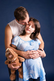 pregnant woman and her husband embracing poster