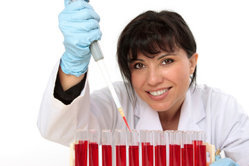 biologist, holding a pipette with sample from test tubes.