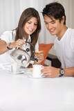 young couple having breakfast at home looking happy