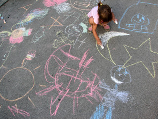little girl drawing on the street