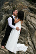 Happy bride and groom kissing on top of a mountain.