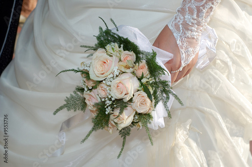 Brides's hand in lacy signet with wedding bouquet