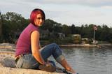 Girl ssitting on lakeshore. poster