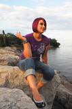 Girl sitting on lakeshore. poster