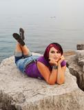 Girl lying on lakeshore. poster