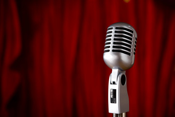 A silver vintage microphone in front of a red stage curtain