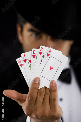 elegant man with Royal Flush Poker Hand - focus on cards