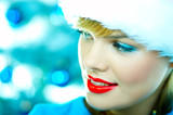 Beautiful woman wearing santa hat next to christmas tree