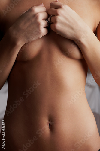 Naked young adult caucasion woman holding on to her breasts