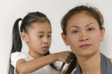 Asian Mom is having her hair braided by her daughter poster