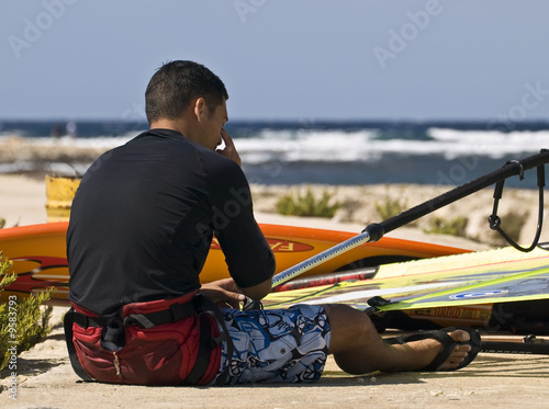A young windsurfer resting ashore before hitting the waves