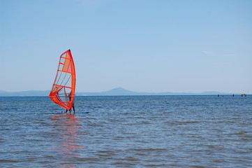 Windsurfer surfing on calm coastal water