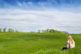 Girl sits on a grass and hold look far away poster