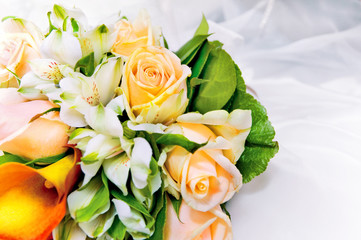 wedding bouquet of fresh flowers against white dress