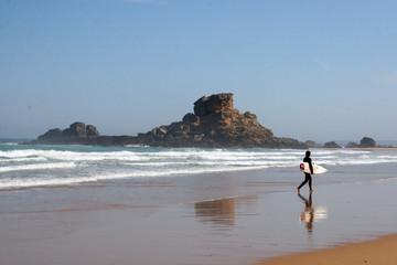 hombre caminando con tabla de surf