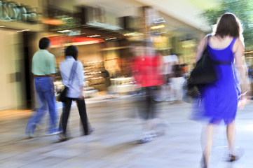 People shopping in a mall, panning shot, intentional motion blur