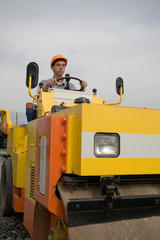 The worker operates a steamroller.