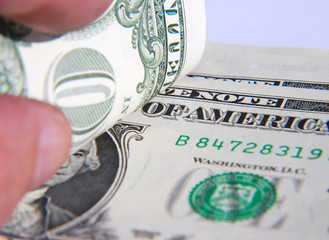 Hand holding American dollar notes focused on writing