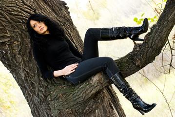 beautiful melancholic girl sitting on the tree