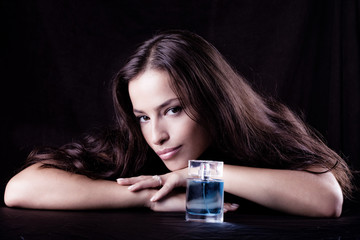 woman with bottle of perfume, studio dark background