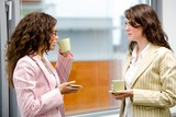 Young businesswomen having break at office drinking coffee poster