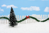 Evergreen tree and white picket fence with green garland poster