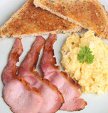 Scrambled eggs with grilled back bacon and toast poster
