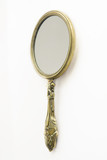 Ornate Antique Art Deco brass hand-mirror. Isolated on white