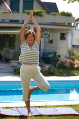 Happy active senior woman doing yoga exercise at home,