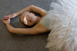 smiling ballerina is relaxing on the floor