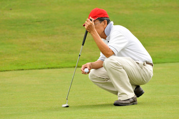 Senior golfer is assessing the contours of the green.