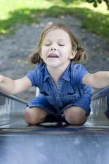 little girl wearing a blue dress climbing on the slide