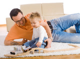 Father and kid playing together on floor of livingroom, smiling. poster