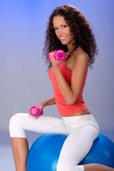 Pretty girl doing weight exercise on the big blue ball