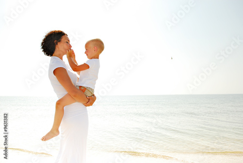 young woman holding a young boy on a beach