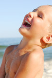 Close up portrait of young boy laughing with delight by sea. poster