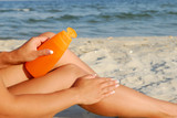 Woman applying lotion to leg on sandy beach by water. poster