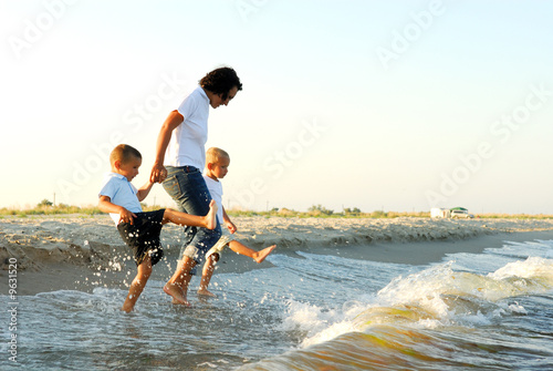woman holding hands of two young boys, as they splash in water