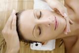 young female enjoying a facial massage or healing poster