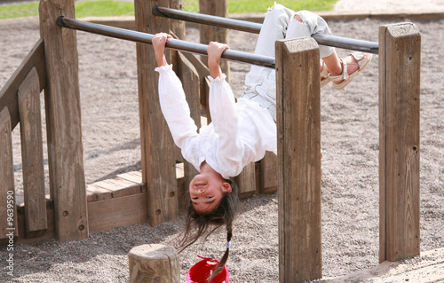 Little girl hanging upside down on parallel bars at playground