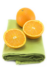 Oranges on a green folded cloth placemat, isolated on white.