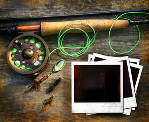 Fly fishing rod with pictures on wood background