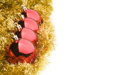 Four red Christmas balls in a row, over gold tinsel garland