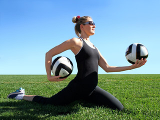 Young pretty woman exercising on green grass
