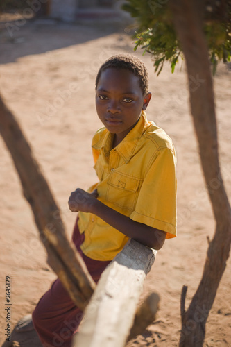 african boy with yellow shirt sitting in the shade