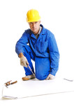 workman sitting on the floor near the blank paper for blueprints poster