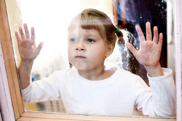 Portrait of a young girl  stands outside the window.